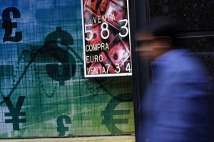 A pedestrian walks past a money exchange bureau with a board displaying the exchange rate of the U.S. dollar against the Chilean Peso, in downtown Santiago October 30, 2014. REUTERS/Ivan Alvarado